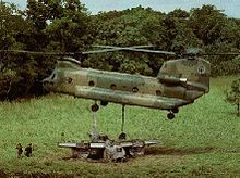 Colour photo of a twin-rotored helicopter flying just above the wreckage of an aircraft