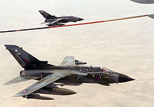 Photograph of a pair og Toranados over the desert and bewlo a fuel hose (for in-flight refueling).