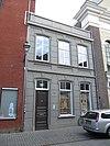 foto van Huis met gebosseerd gepleisterde lijstgevel, bekroond door een attiek en voorzien van segmentvormig overtoogde vensters
