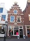 foto van Pand met renaissance trapgevel, versierd met natuurstenen banden, blokken en geprofileerde waterlijsten en bekroond door een topfronton