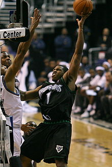 A basketball player wearing a black jersey with the number 1 on it shooting the ball.