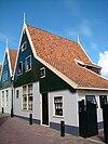 foto van Huis met houten topgevel boven een bakstenen gepleisterde pui