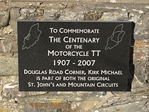 Plaquette in Kirk Michael die herinnert aan het 100-jarige bestaan van de Isle of Man TT. Kirk Michael lag langs de St John's Short Course, maar ook langs de Highroads Course, de Four Inch Course en de Snaefell Mountain Course