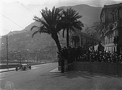A large, open sports car drives past crowds of people and palm trees, with the city of Monaco in the background