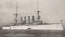 A large white warship at anchor in a calm sea, with a small boat alongside