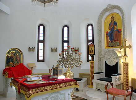 The Holy Place (Sanctuary) in the church of the Saint Vladimir Skete at Valaam Monastery. To the left is the Holy Table (altar) with the Gospel Book, the Tabernacle, and the seven-branch candlestand. The Table of Oblation is in the background to the left. To the right is the Cathedra (Bishop's Throne). Saint Vladimir Skete (Valaam Monastery) 14.jpg