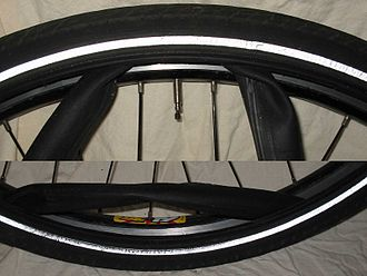 Bicycle tire - A tubed, clincher tire showing the inner tube protruding between the tire and the rim