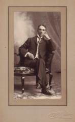 Seated man by T E Hopkins of McPherson Kansas USA.png