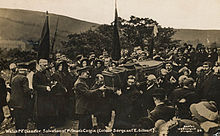 A Salvation Army funeral cortege, with men carrying the coffin. The streets are lined with people, some of whom have Salvation Army banners.