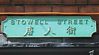 A street sign, painted green, bearing the name Stowell Street and three Chinese characters