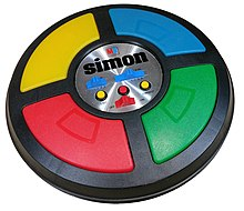 The game is a circular disc divided into four quarter circle buttons each with a different color In the center are the game mode controls