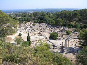 Glanum - Excavations of ancient Glanum, at the foot of Mont Gaussier. The church spire of modern Saint-Rémy-de-Provence can be seen in the middle distance to the left.