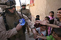 Soldier passes out candies to children during Operation Matador.jpg