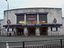 "A wide two-storey stone-faced building has three square entrances at the centre beneath a dark blue awning with the words ""SOUTH WIMBLEDON STATION"". Above the awning is a wide glazed screen in three panels, the centre one of which contains the Underground roundel of a red ring with a blue bar and the word ""UNDERGROUND"". Two smaller roundels either side of the entrances are mounted on poles at right angles to the face of the building."