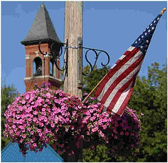 Spencer, Massachusetts - Hanging Basket on Main Street with Town Hall tower in background.