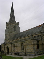 Part of a stone church seen from the southeast, with a protruding south aisle, and a tower surmounted by a spire