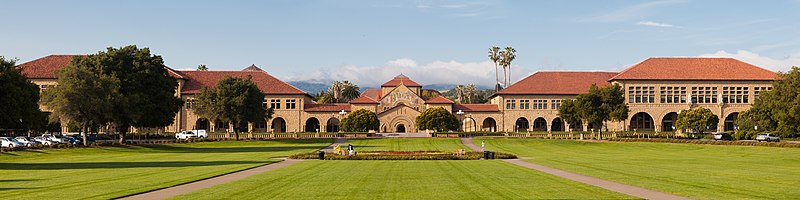 View of the main quadrangle of Stanford University with Memorial Church in the center background from across the grass covered Oval.