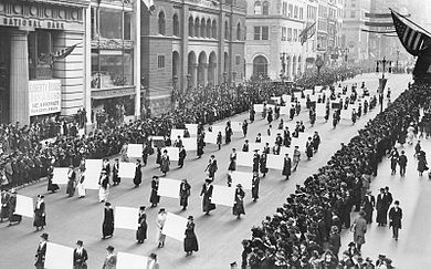 Women's suffragists parade in New York City in 1917, carrying placards with the signatures of more than a million women. Suffragists Parade Down Fifth Avenue, 1917.JPG