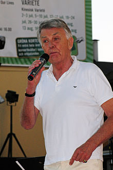 Photograph of Sven-Bertil Taube on a stage, holding a microphone