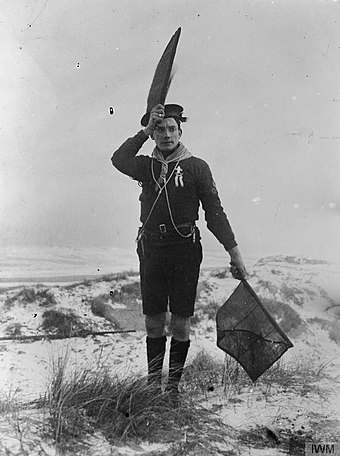 A coast-watching Sea Scout signals to a British warship during the First World War. The Boy Scouts Association in Britain, 1914-1918 Q19966.jpg