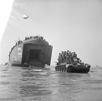3rd County of London Yeomanry (Sharpshooters) - A Cromwell Mk IV tank of the 4th County of London Yeomanry with infantry aboard, comes ashore from an LST, Normandy, 7 June 1944.