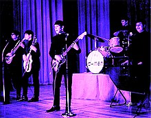 A tinted photograph of five members of the D-Men performing with guitars, drums, and keyboards