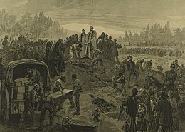 A vicar stands at an open grave, which is being filled with a coffin. Several others are being unloaded from a covered waggon. Crowds of people are shown paying their respects.