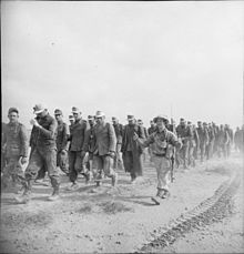 A column of German prisoners walk, from right to left, escorted by a British soldier giving two thumbs up.