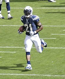 In team warmups and in full Chargers uniform, LaDainian Tomlinson runs with the ball.