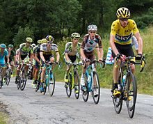 A group of cyclists riding up an incline being led by a one wearing a yellow jersey.