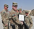 U.S. Army Brig. Gen. Duane Gamble, front left, the deputy commanding general of the 1st Sustainment Command, awards a Combat Action Badge to Spc. Alexus S. Ditto, with the 864th Engineer Battalion, assigned to 131007-A-WQ129-013.jpg