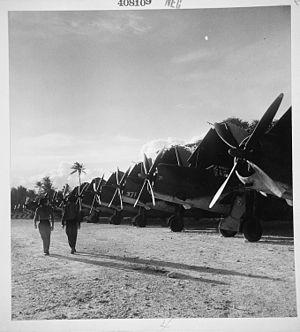 Falalop Airfield - Marines walk past a flight line of SB2Cs on Falalop December 1944