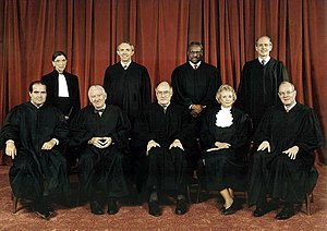 Group photo of United States Supreme Court Justices from 2005. Optional formal dress can be seen under the robes, such as bow ties. Justice Sandra Day O'Connor has added white ruffles.