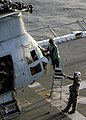 US Navy 030226-N-2321D-001 ircrew clean the windshield of a CH-46 Sea Knight helicopter prior to launching from the flight deck aboard USS Boxer (LHD 4).jpg