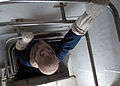 US Navy 030312-N-0068T-030 Fireman Charles Phillips makes his escape through an emergency escape trunk.jpg