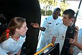 US Navy 050428-N-9594C-003 Operations Specialist 2nd Class Oliver Williams, center, assigned to Naval Recruiting District Miami, seats Courtney Perry and Armando Munoz into a F-A-18 Hornet aircraft simulator.jpg
