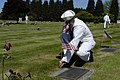 US Navy 050527-N-6477M-209 Seaman Christopher A. Racca, assigned to the Nimitz-class aircraft carrier USS Abraham Lincoln (CVN 72), places an American flag at the headstone of a veteran.jpg