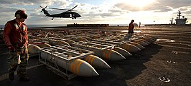 US Navy 051104-N-2984R-169 Aviation Ordnancemen assigned to Weapons Department prepare pallets of BLU-117 2,000-pound general-purpose bombs to be airlifted.jpg