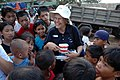 US Navy 070602-N-2296G-146 U.S. Navy Cmdr. Joan Cooper attached to reserve Operational Health Support Unit Dallas, Texas, Det. H gets a rock star greeting from the children of Isabela City who want to see her big toothbrush as.jpg
