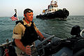 US Navy 070604-N-0684R-131 Seaman Kevin Bruton, from the visit, board, search and seizure (VBSS) team assigned to guided-missile destroyer USS Preble (DDG 88), steers a rigid hull inflatable boat around a local tugboat after dr.jpg