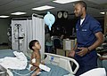 US Navy 080607-N-0209M-007 Three-year-old Jose Angelo Dacuycuy and Hospital Corpsman Daniel Garrett play with a balloon after Dacuycuy received surgery to correct his Hirschsprung's disease.jpg