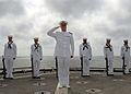 US Navy 081006-N-3392P-034 Sailors assigned to the ceremonial detail of the amphibious dock landing ship USS Carter Hall (LSD 50) render honors during a burial at sea for a deceased Navy veteran.jpg