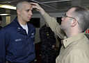 US Navy 090225-N-4014G-008 Air Traffic Controller 2nd class Alejandro Nieves receives the Imposition of Ashes from Navy Chaplain Lt. Chris Stanfield during an Ash Wednesday Mass in the chapel aboard the aircraft carrier USS Dwi