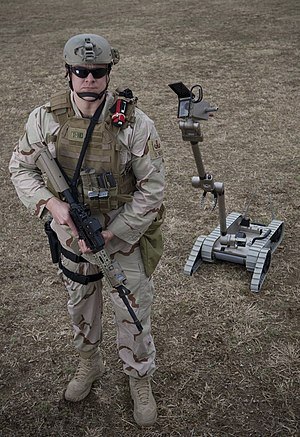 PackBot - A U.S. Navy Sailor assigned to an explosive ordnance disposal team poses beside a PackBot.
