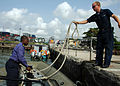 US Navy 090323-N-1655H-077 Boatswain's Mate 3rd Class Joseph Kluempers, assigned to the amphibious dock landing ship USS Nashville (LPD 13), tosses a line to a Nigerian officer.jpg
