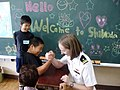 US Navy 090515-N-1334U-001 Lt. j.g. Mary Robinson arm wrestles with a 6th grader from Shimoda Elementary School in Shimoda, Japan.jpg