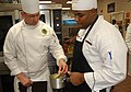 US Navy 090730-N-4698K-249 Food Network Chef Robert Irvine gives Culinary Specialist 2nd Class Andre Keith, pointers during the cooking portion of the 2009, Navy Region Southeast Iron Chef Competition.jpg