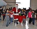 US Navy 091212-N-6999T-005 Children from the Make-A-Wish Foundation escort Santa to his chair during their visit to Navy Air Squadron VR-57.jpg