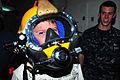 US Navy 110609-N-BT122-635 Navy Diver 2nd Class Chance Griffith observes a guest wearing an MK 21 diving helmet during a Friends and Family Day Cru.jpg
