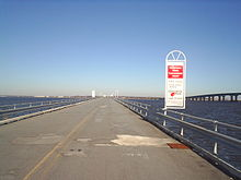 A two lane road on a low bridge over a large body of water with a higher span seen to the right